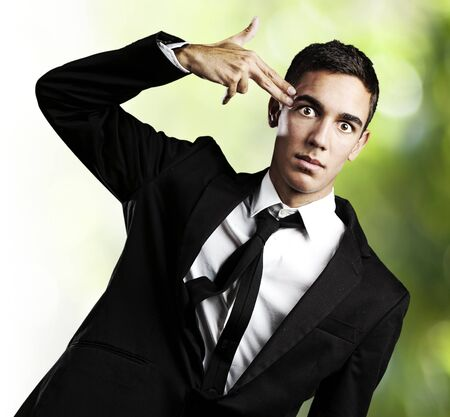 portrait of business man gesturing suicide against a abstract background photo