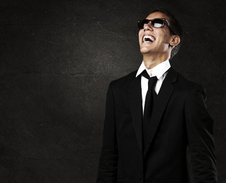 portrait of business man with sunglasses laughing against a grunge background photo