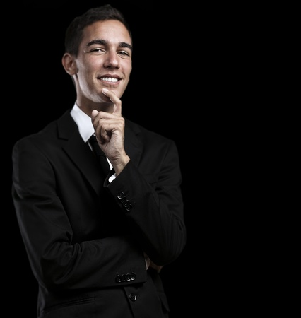 portrait of handsome young business man thinking and looking up against a black background photo