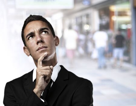 portrait of business man thinking against a crowded place photo