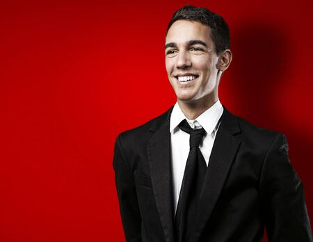portrait of young business man smiling against a red background photo