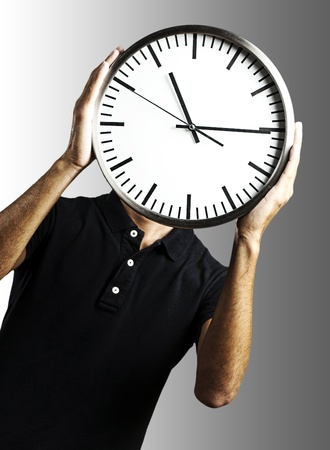 young man covering his face with a clock over grey background photo
