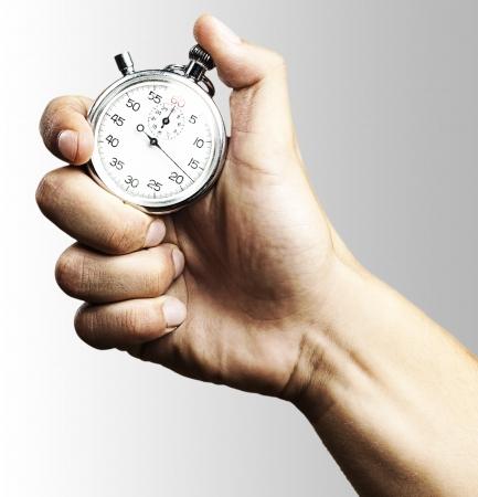 main tenant un chronomètre sur un fond gris Banque d'images