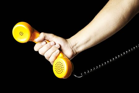 telephone receiver: hand holding a yellow vintage telephone over black background