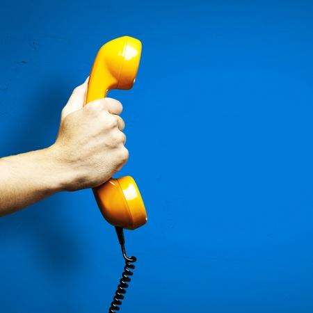 Hand houden van ouderwetse telefoon ontvanger geïsoleerd op blauwe achtergrond