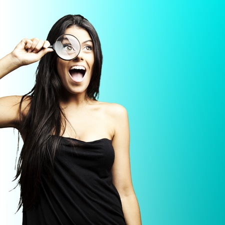 portrait of woman excited looking through a magnifying glass over blue background photo