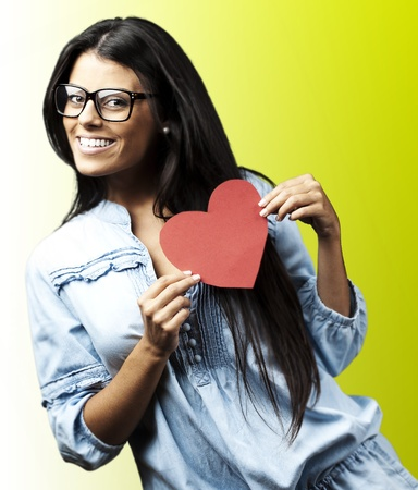 portrait of young woman holding a heart against a green background photo