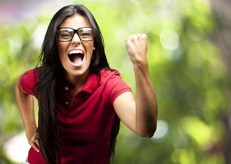 woman shouting: portrait of young woman gesturing victory against a nature background