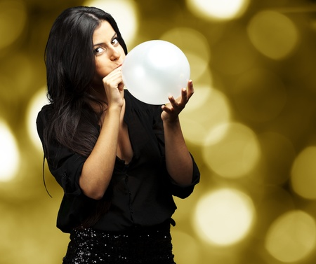 portrait of young woman blowing balloon against a abstract lights background photo