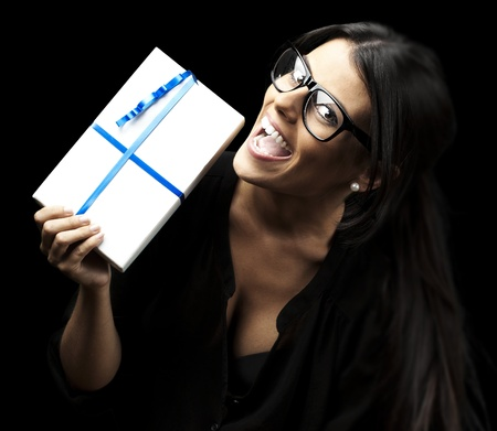 portrait of pretty woman showing a gift over black background photo