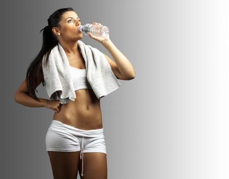 portrait of young woman wearing sport clothes and drinking water against a grey background photo