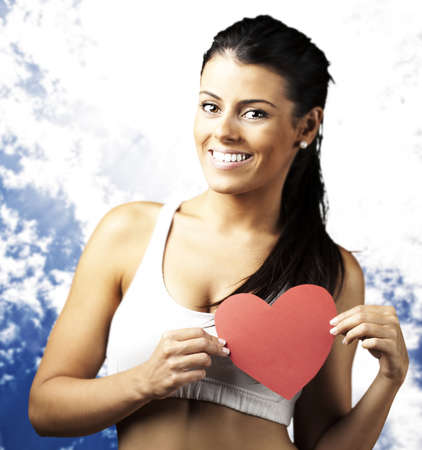 portrait of healthy woman holding red heart symbol against a blue sky background photo