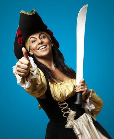 pirata mujer: retrato de una mujer pirata sosteniendo una espada y un gesto bien contra un fondo azul