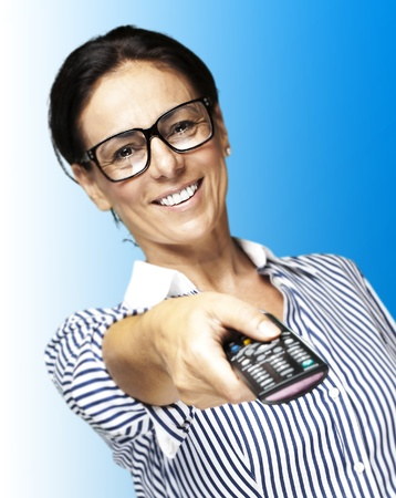 portrait of middle aged woman wearing glasses using a remote control tv over white background photo