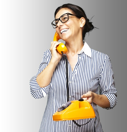 portrait of middle aged woman wearing glasses with vintage telephone on grey photo