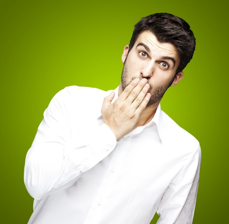 quiet adult: portrait of young man covering his mouth with hand over green Stock Photo