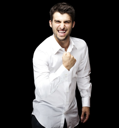 portrait of young man winner gesture against a black background photo