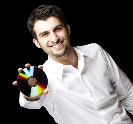 portrait of a handsome young man holding cd against a black background photo