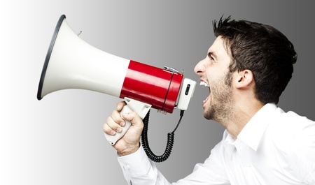 portrait of young man handsome shouting using megaphone over grey background photo