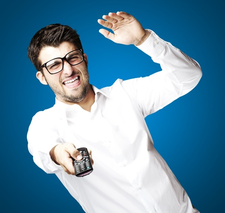 portrait of angry young man using tv control over blue background photo