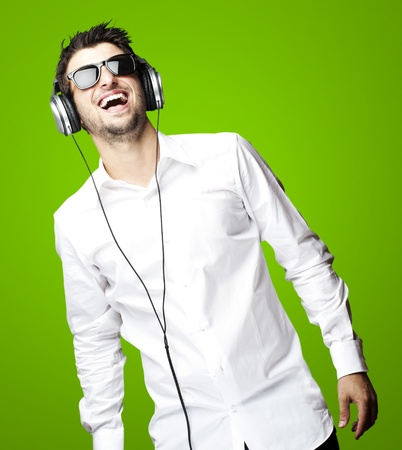 portrait of a handsome young man listening to music with headphones over green background photo
