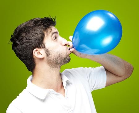 Портрет молодой человек дует воздушном шаре над зеленым фоном