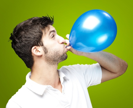 Porträt junger Mann bläst einen Ballon auf grünem Hintergrund