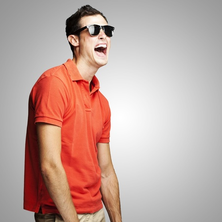 portrait of young man with sunglasses laughing over grey background photo