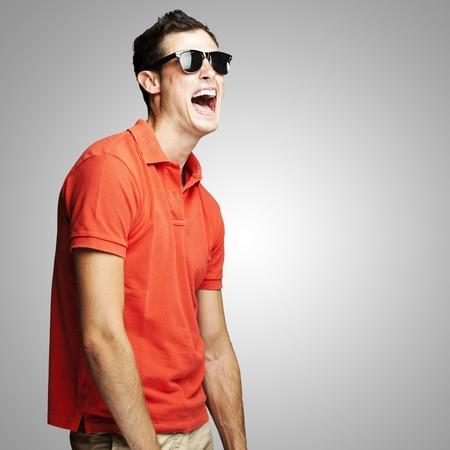 giggle: retrato de hombre joven con gafas de sol riendo sobre fondo gris
