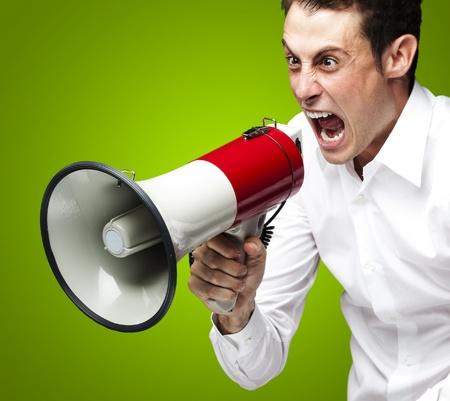 portrait of young man screaming with megaphone against a green background photo