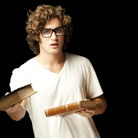 portrait of young student holding books over black background photo