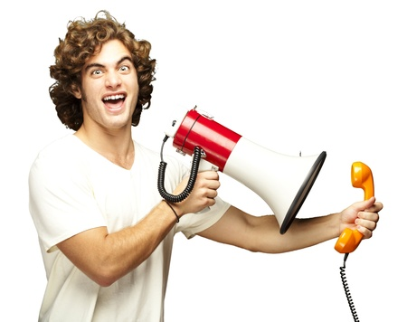 portrait of young man shouting with megaphone and talking on vintage telephone over white photo