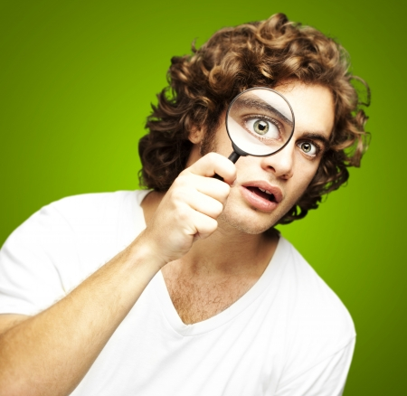 portrait of young man looking through a magnifying glass against a green background photo