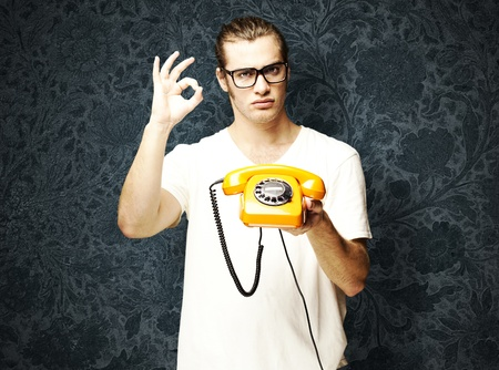 young man holding a vintage telephone and gesturing against a vintage background photo
