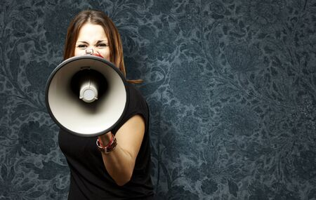 portrait of young woman shouting with megaphone against a vintage wall photo