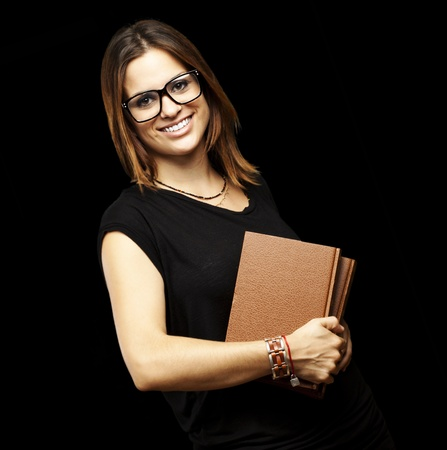 portrait of young student with glasses holding a old book over black background Stock Photo - 11507625