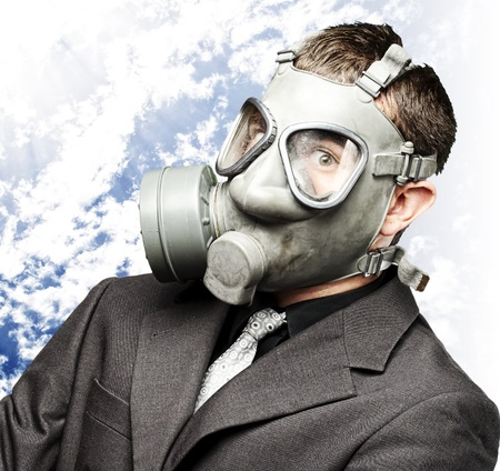 portrait of business man with gas mask against a cloudy sky background photo