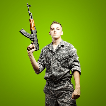 portrait of young soldier holding rifle wearing urban camouflage over green background photo