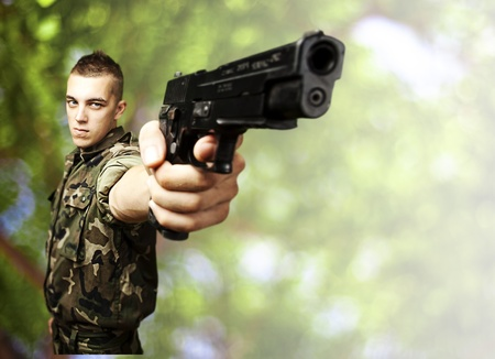 man holding gun: portrait of young soldier aiming with gun against a nature background Stock Photo