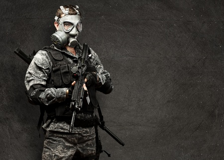 portrait of young soldier with gas mask and rifle against a grunge background photo
