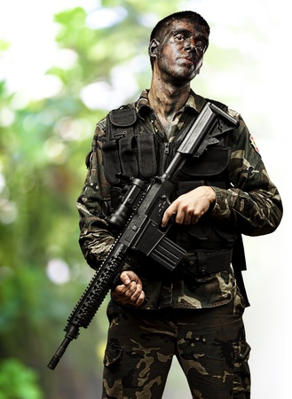 portrait of young soldier with camouflage paint holding rifle in the jungle  Stock Photo - 11507709