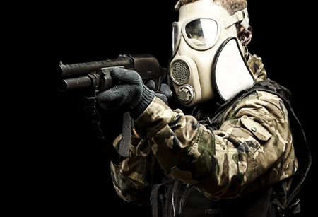 security vest: portrait of young soldier with gas mask aiming with shotgun