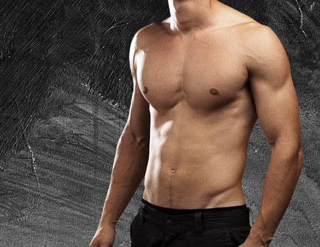 strong torso of young man against a grunge wall Stock Photo - 11232278