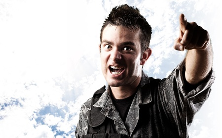indicating: portrait of young soldier pointing with finger against a cloudy sky background