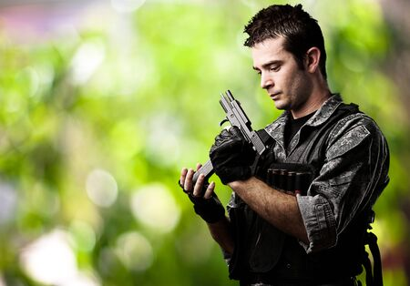reloading: portrait of young soldier reloading the gun against a wild background Stock Photo