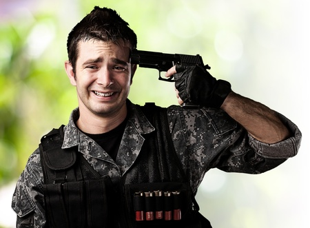 portrait of young soldier committing suicide against a wild jungle background photo