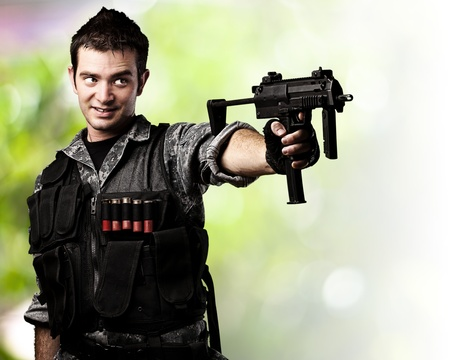 pointing gun: portrait of young soldier aiming with rifle against a wild background