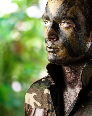 face guard: portrait of young soldier face painted with jungle camouflage in the jungle