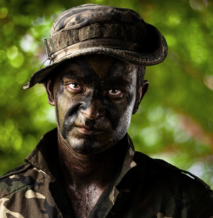 portrait of young soldier face painted with jungle camouflage in the jungle photo