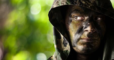 american soldier: portrait of young soldier face with hood and painted with jungle camouflage in the jungle Stock Photo